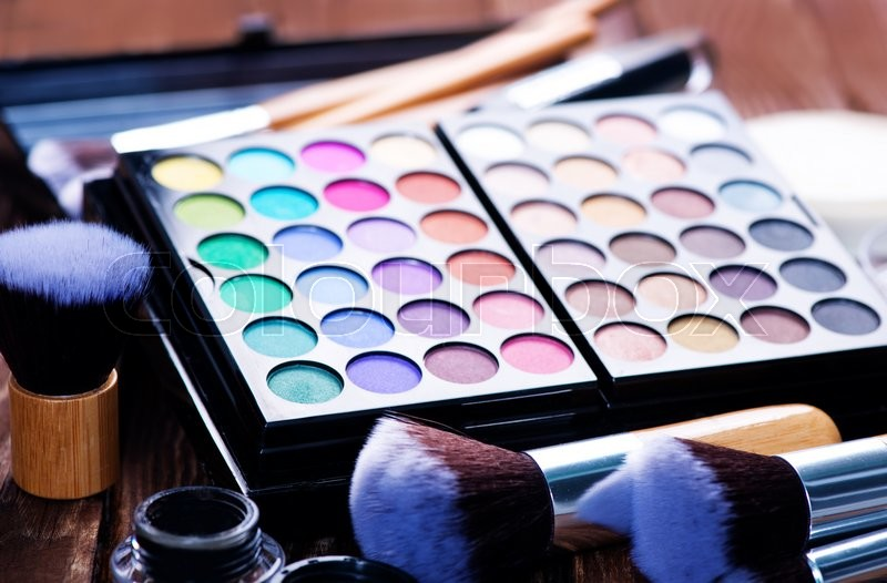 Stock image of 'Various makeup products on dark background with copyspace'