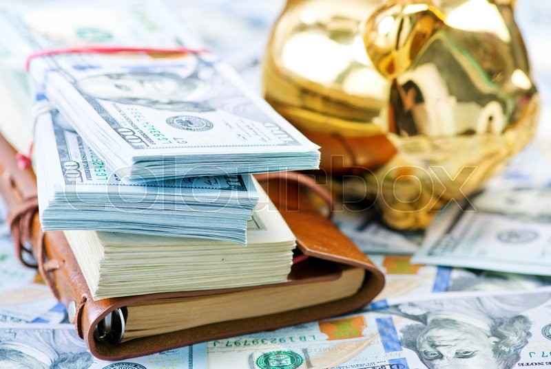 Stock image of 'Piggy bank and money on a table'
