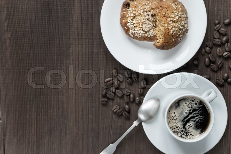 Stock image of 'Black coffee with froth in white porcelain cup, coffee beans and oatmeal cookies on a dark wooden background, top view'