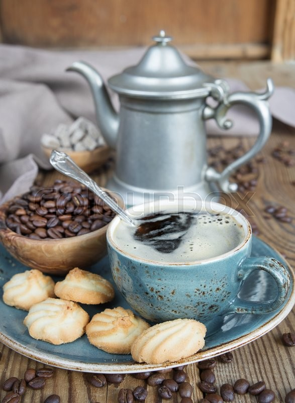 Stock image of 'Blue cup of black coffee, cookies and coffee pot  surrounded by linen cloth, sugar pieces and coffee beans on old wooden table'