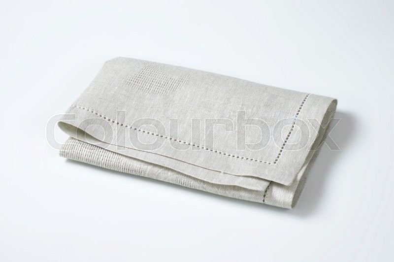 Stock image of 'folded light grey cloth place mat'