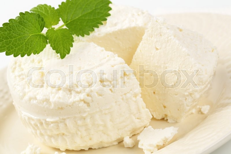 Stock image of 'wheel of fresh curd cheese on plate'