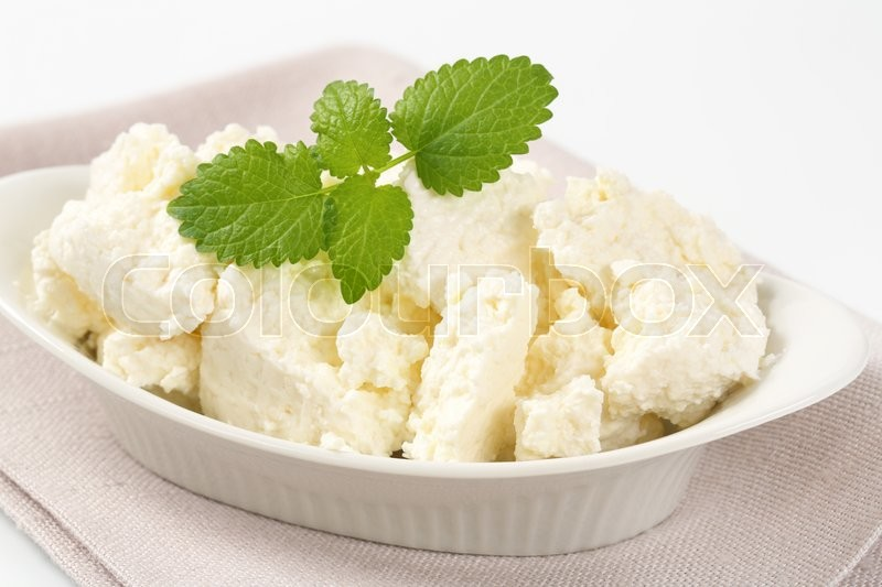 Stock image of 'pieces of fresh curd cheese in white bowl'