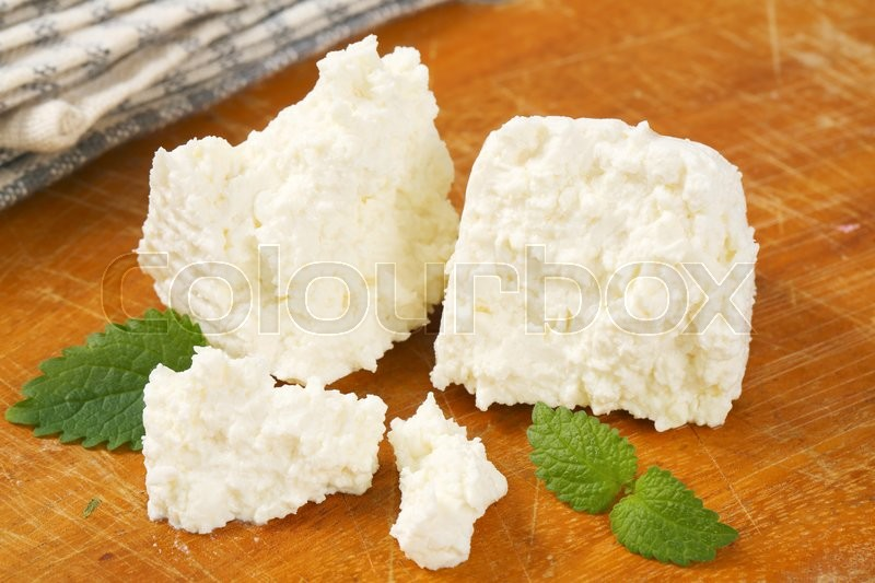 Stock image of 'pieces of fresh curd cheese on cutting board'