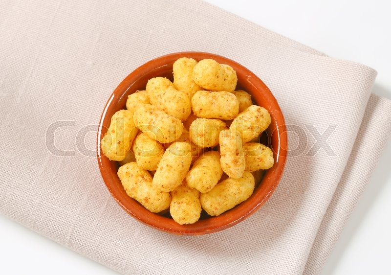 Stock image of 'crunchy peanut puffs in terracotta bowl'