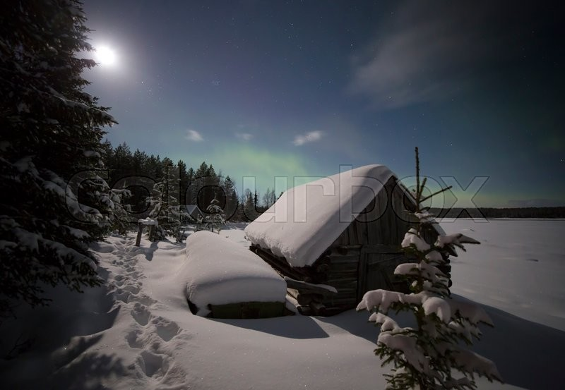 Stock image of 'Village house in the lights of moon and Aurora borealis. Northern Karelia. Russia.'