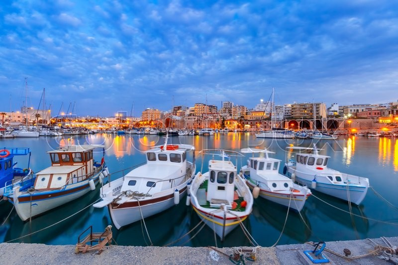 Stock image of 'Old harbour of Heraklion with fishing boats and marina during twilight blue hour, Crete, Greece. Boats blurred motion on the foreground.'