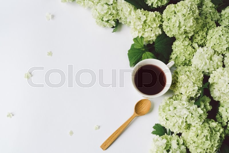 Stock image of 'Green flowers, yellow cup with tea and a wooden spoon on a white background, top view, space for text'