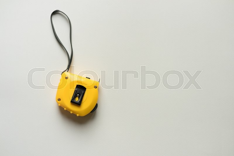 Stock image of 'Yellow measuring tape on a white table, top view, space for text'