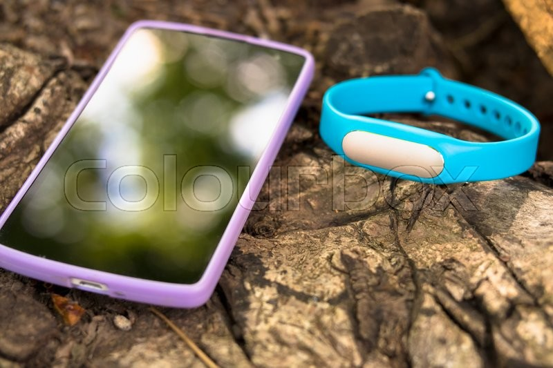 Stock image of 'Fitness tracker and smart phone lying on a tree stump in the forest'