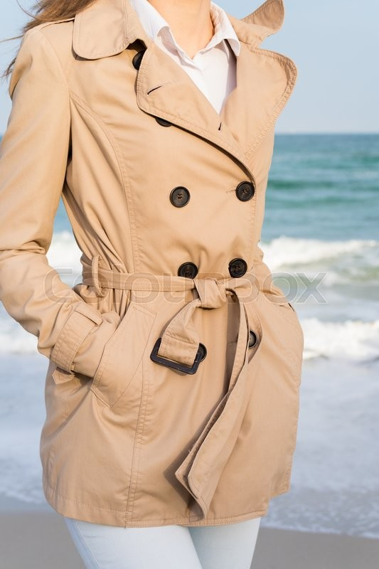 Stock image of 'Slender girl in a beige coat and jeans walking along the beach in the evening sun'