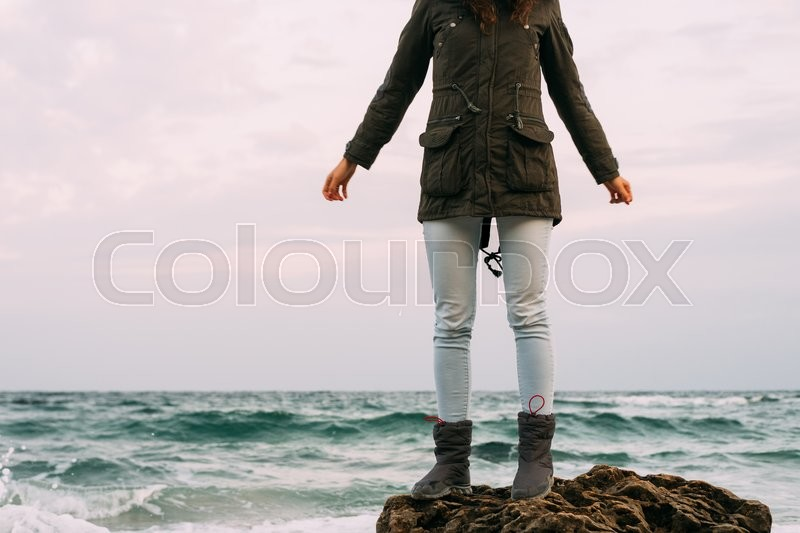 Stock image of 'Girl in the green jacket, jeans and boots stands on a rocky stone on the beach in cloudy weather'