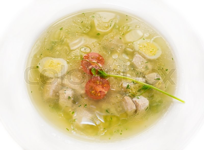Stock image of 'Broth with pasta greens and quail egg in a white plate'