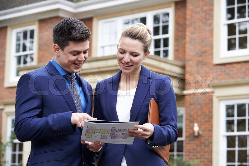 Stock image of 'Male And Female Realtor Standing Outside Residential Property'