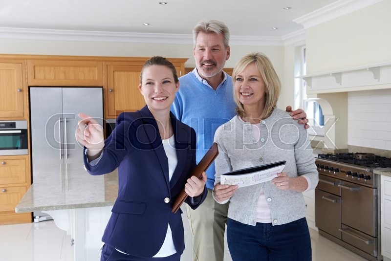 Stock image of 'Female Realtor Showing Mature Couple Around House'
