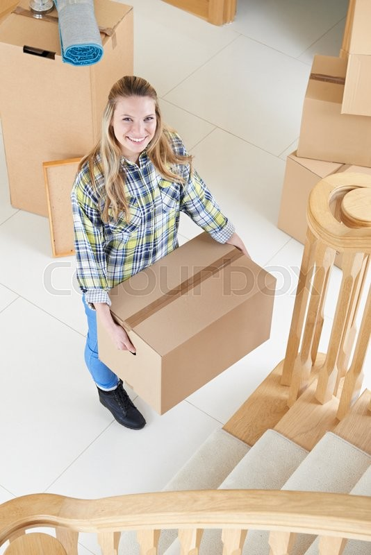 Stock image of 'Portrait Of Young Woman Moving Into New Home'