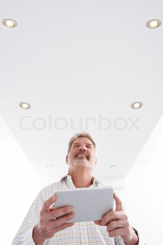 Stock image of 'Man Controlling Lighting With App On Digital Tablet'