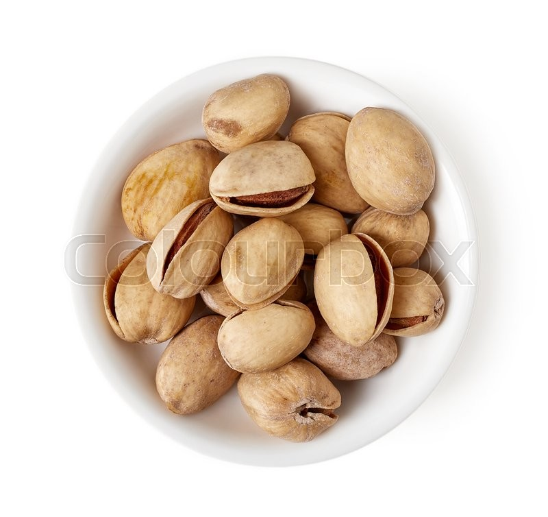 Stock image of 'Bowl of salted roasted pistachios isolated on white background, top view'