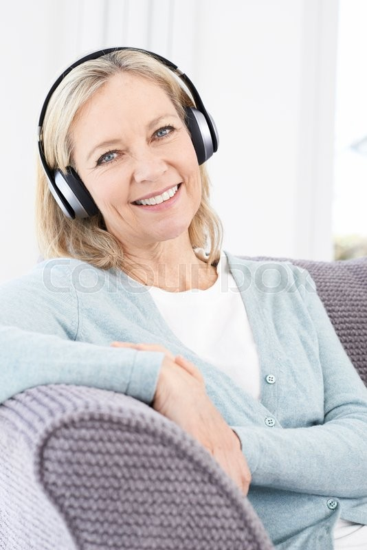 Stock image of 'Mature Woman Listening To Music On Wireless Headphones'