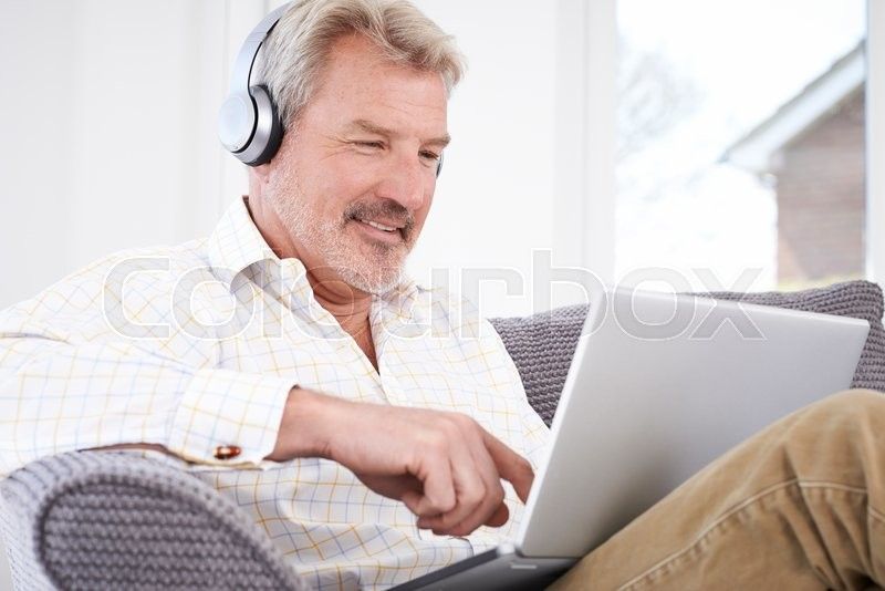 Stock image of 'Mature Man Streams Music From Laptop To Wireless Headphones'