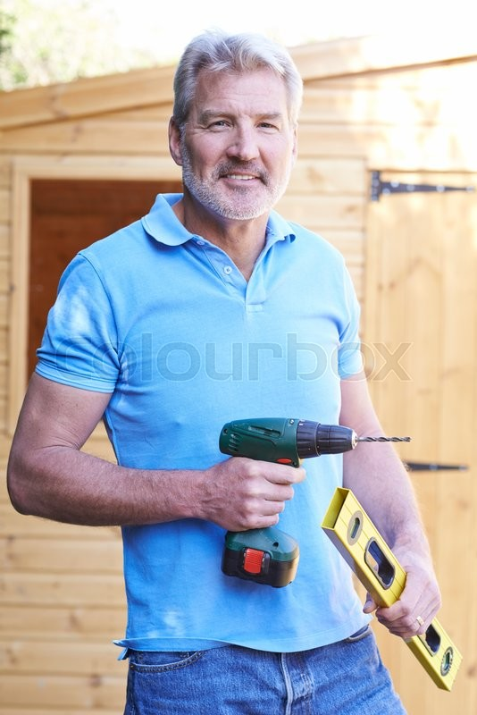 Stock image of 'Handyman Standing Outside Garden Shed With Tools'
