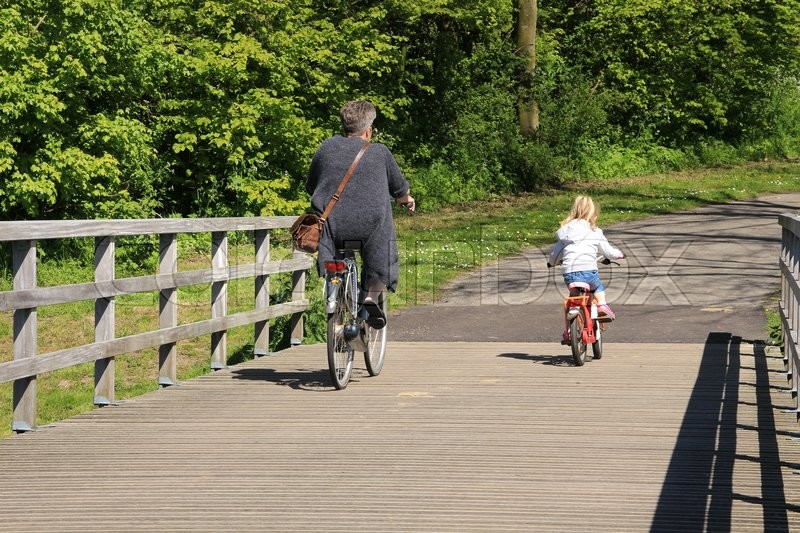 Stock image of 'Grandmom and the little girl are biking over the wooden bridge in the wonderful park in the summer.'