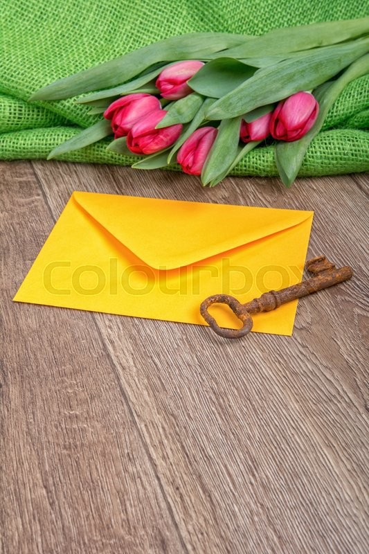 Stock image of 'Envelope, rusty key and red tulip on a wooden background'