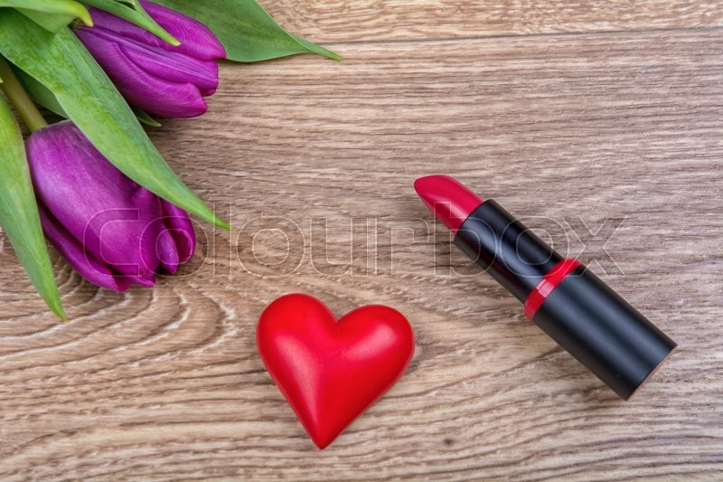 Stock image of 'Lipstick, red heart and purple tulips on a wooden background'