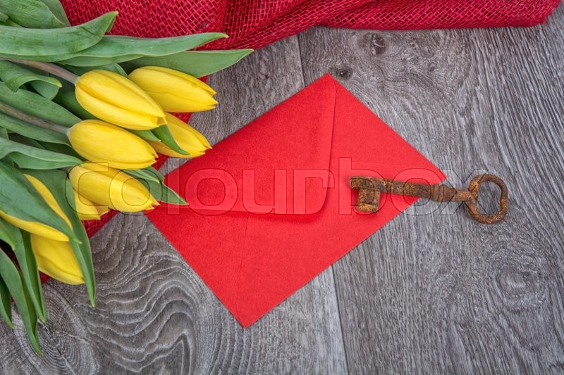 Stock image of 'Envelope, rusty key and yellow tulip on a wooden background'