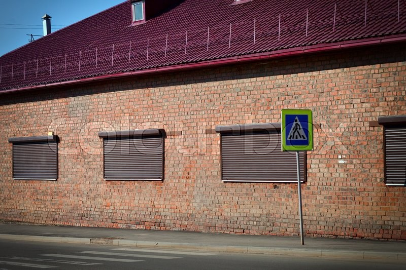 Stock image of 'The brick building with closed shutters and pedestrian crossing sign'