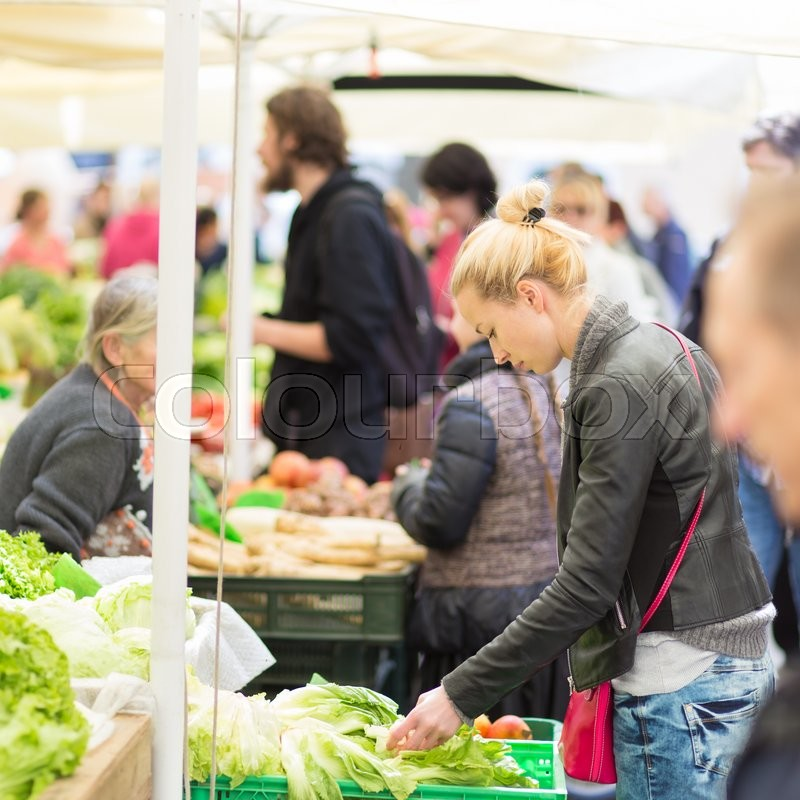 Stock image of 'Woman buying fruits and vegetables at local food market. Market stall with variety of organic vegetable.'