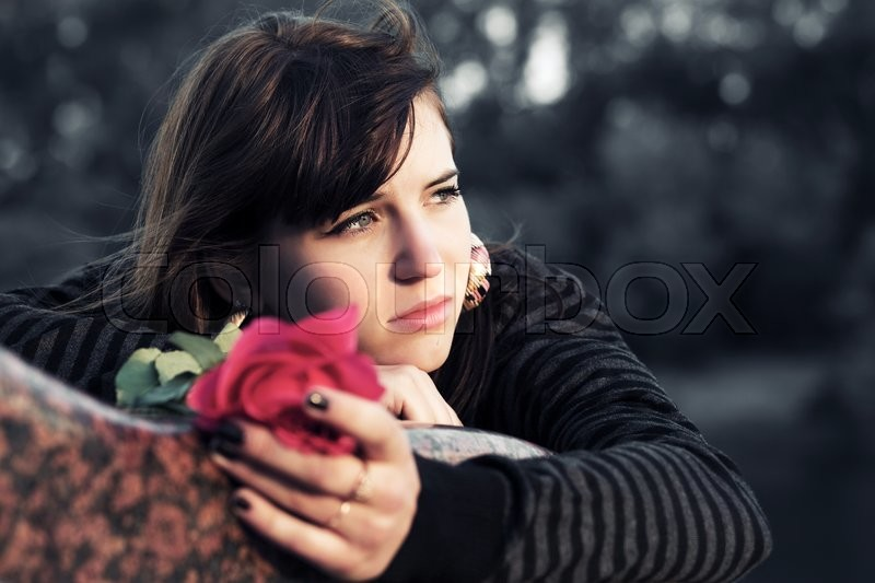 Stock image of 'Sad young woman with a red rose '