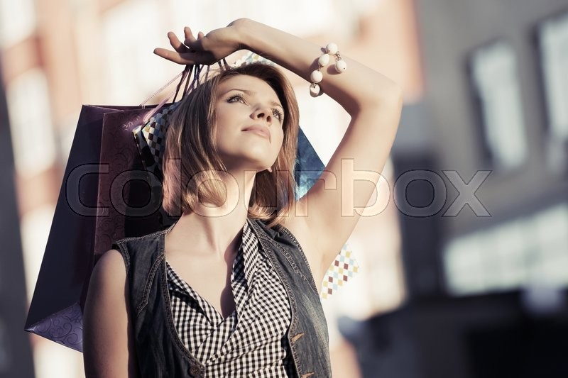 Stock image of 'Happy young woman with shopping bags '