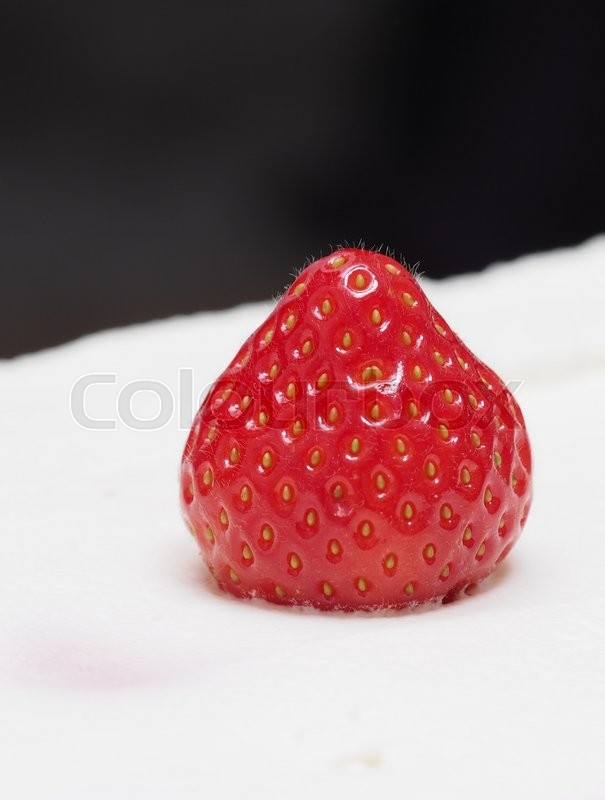 Stock image of 'A strawberry on a cream cake'