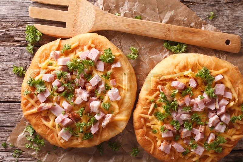 Stock image of 'Hungarian pancakes langos with ham and cheese close-up on the table. horizontalview from above\'
