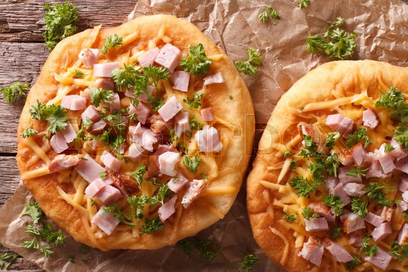 Stock image of 'langos deep fried with cheese and ham close-up on the table. Horizontal view from above\'