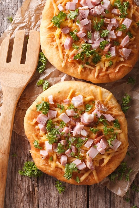 Stock image of 'Hungarian pancakes langos with ham and cheese close-up on the table. Vertical view from above\'