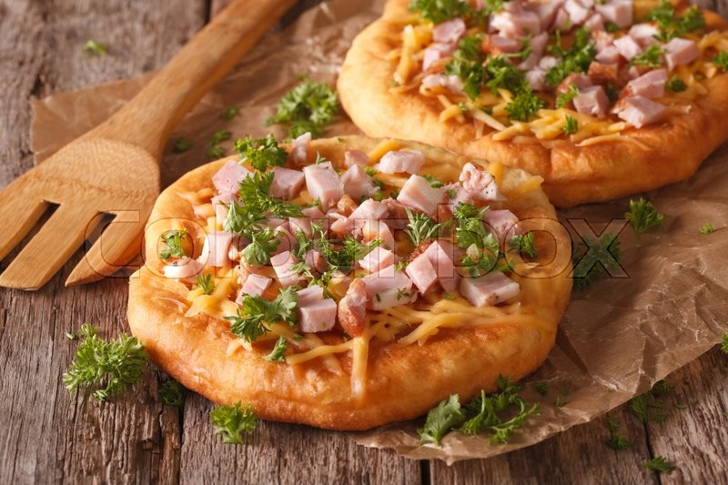 Stock image of 'Hungarian pancakes langos with ham and cheese close-up on the table. horizontal\'