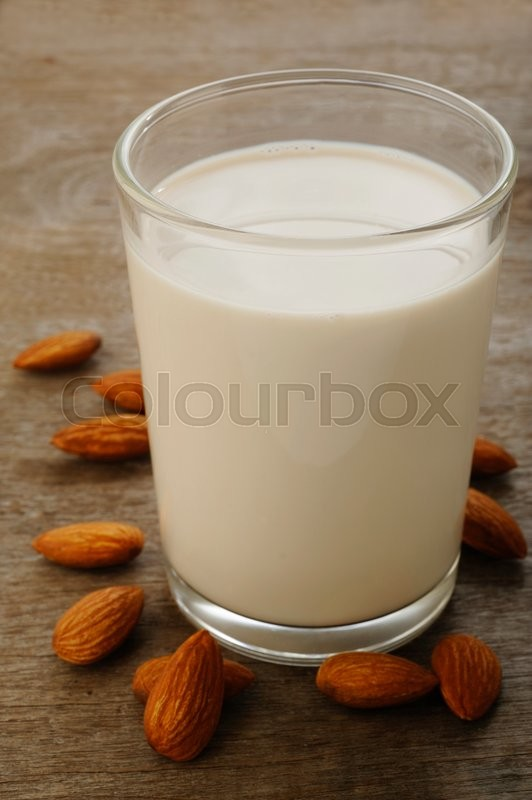 Stock image of 'almond milk in glass with almonds'