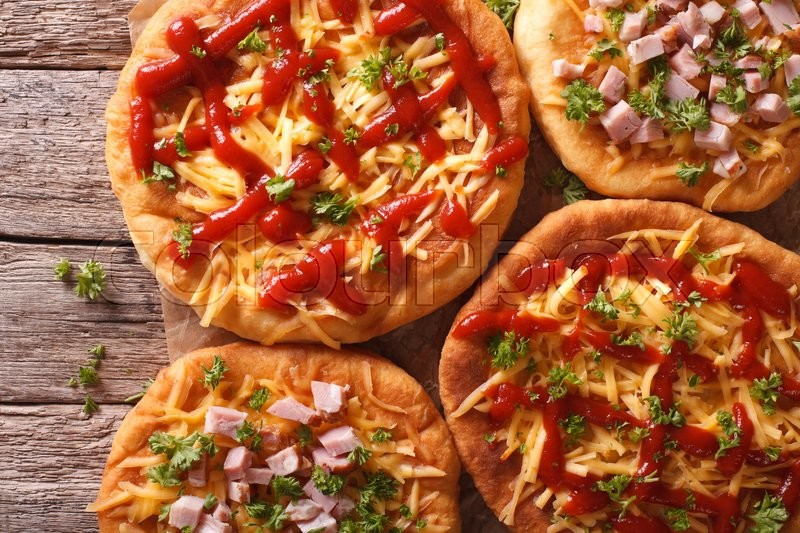 Stock image of 'Hungarian hot langos with cheese, ketchup and ham close-up on the table. Horizontal view from above\'