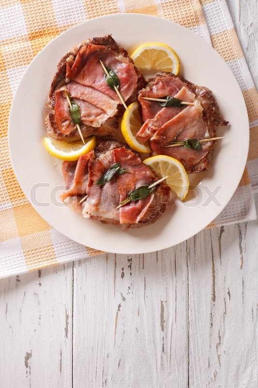 Stock image of 'Italian cuisine: beef saltimbocca with lemon close up on a plate. Vertical view from above\'