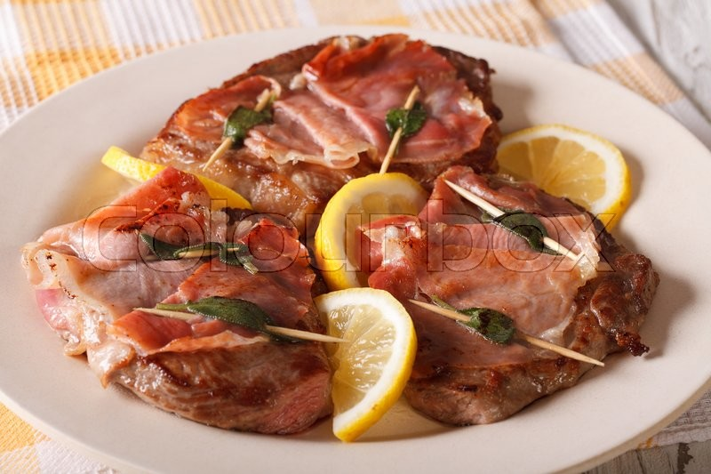 Stock image of 'Italian beef Saltimbocca with sage, ham and lemon close-up on a plate. horizontal\'