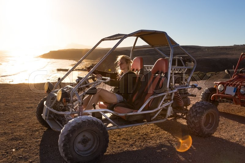 Stock image of 'Active woman driving quadbike on dirt road by the sea in sunset.'