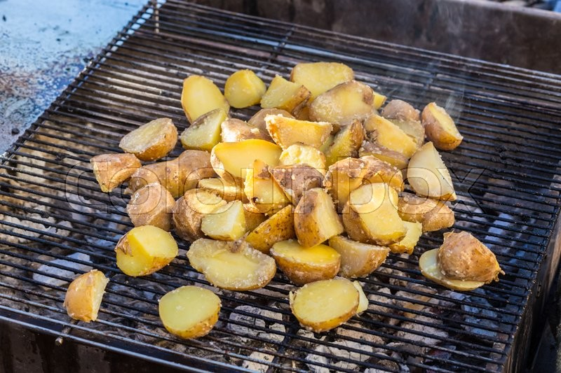 Stock image of 'Roasted potatoes on barbeque.'