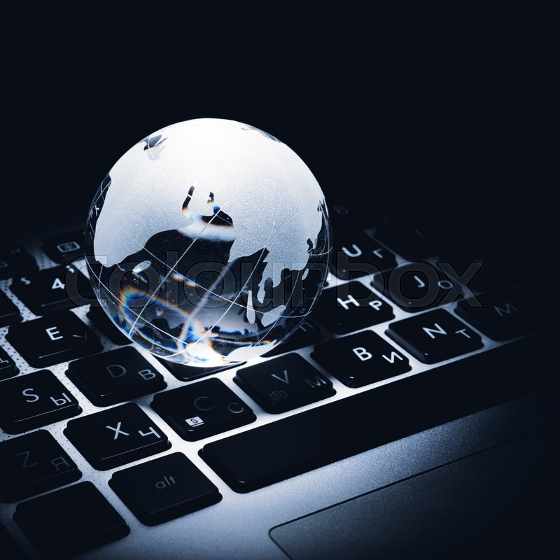Stock image of 'Business concept of a glass globe on a laptop keyboard'