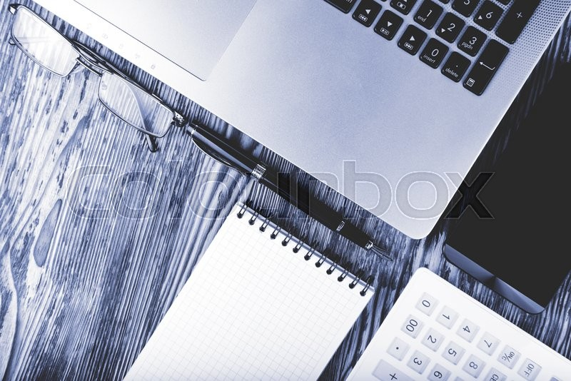Stock image of 'Business concept of laptop, smart phone, notebook, pen on a wooden table'