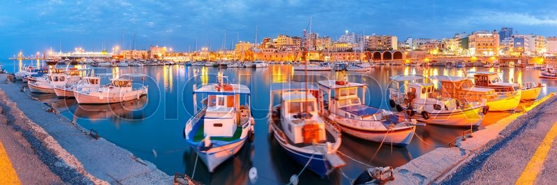 Stock image of 'Panorama of Old harbour with fishing boats and marina during twilight blue hour, Heraklion, Crete, Greece. Boats blurred motion on the foreground.'