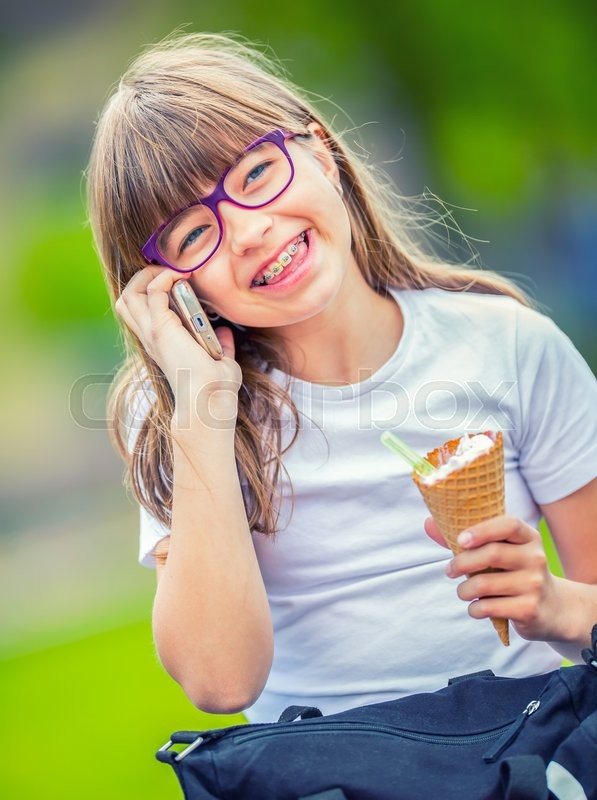 Stock image of 'Cute little girl in the park on a sunny day with ice cream and mobile phone.'