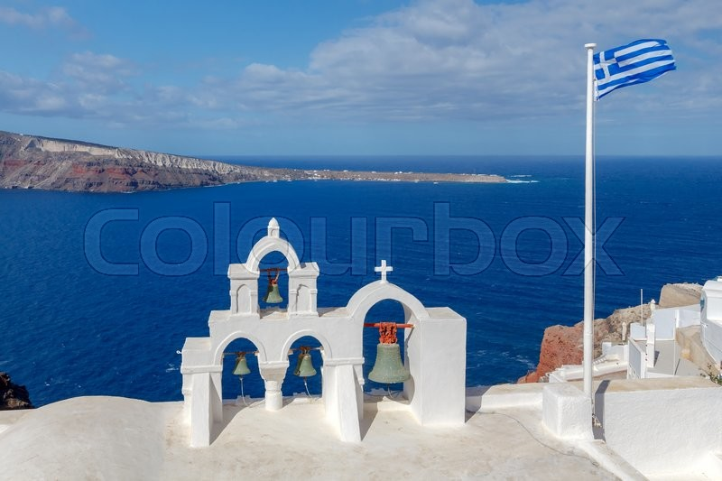 Stock image of 'Christian church with  bell tower and Greek flag over the bay on a sunny day in the village  Oia.'