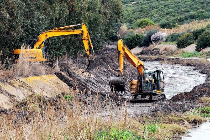 Stock image of 'Large excavators engaged in cleaning of the riverbed of a river from the mud and debris.'